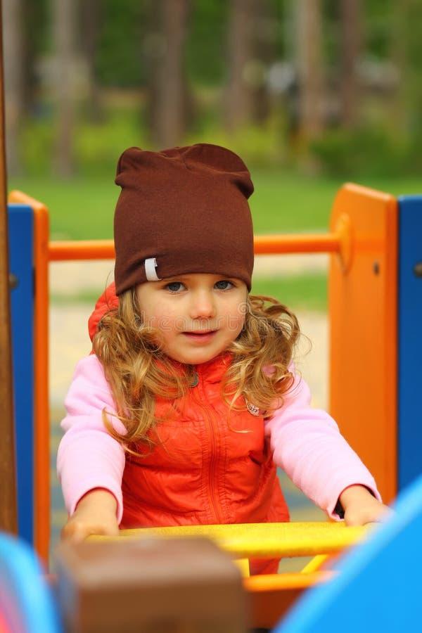 Porträt eines glücklichen Kleinkindmädchens, welches das Lenkrad auf dem Spielplatz dreht lizenzfreie stockfotografie