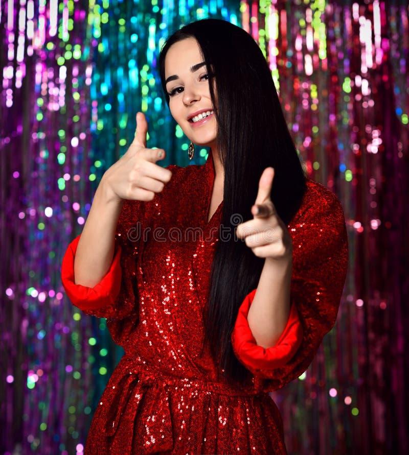 Porträt eines glücklichen lächelnden Mädchens in einem stilvollen bezaubernden roten Kleid mit Hauchen an einer Modepartei stockbild