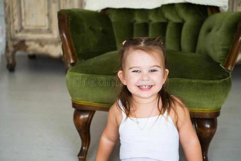 Porträt eines glücklichen lachenden Kindermädchens, das auf dem Boden nahe dem antiken Stuhl sitzt stockfoto