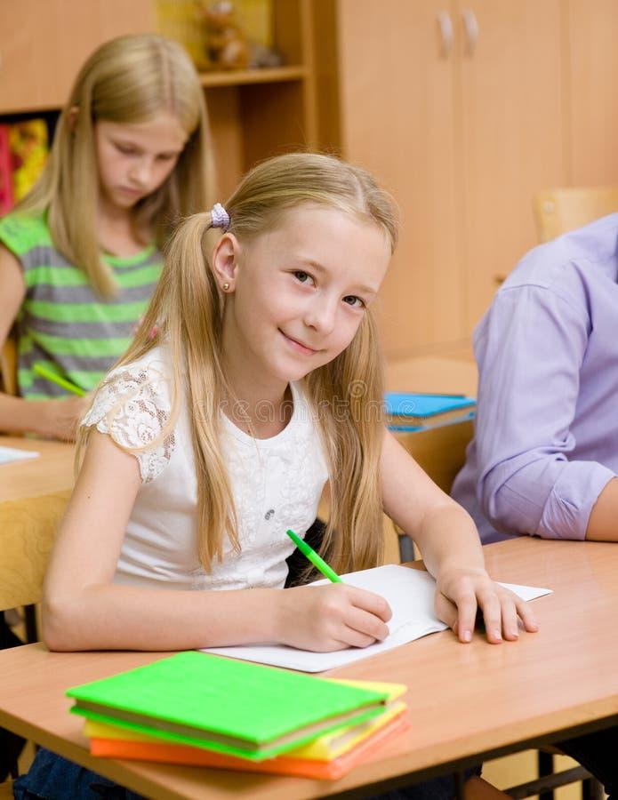 Porträt eines glücklichen Mädchens, das in ein Übungsbuch während der Prüfung schreibt lizenzfreies stockbild