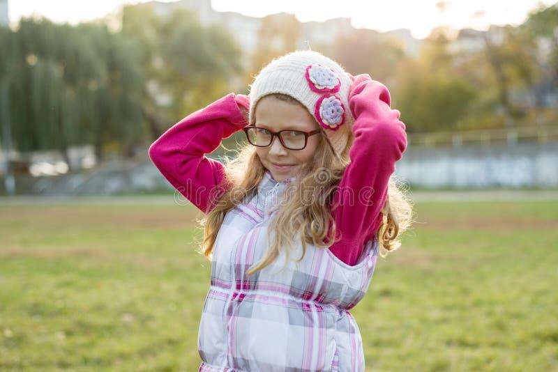 Porträt eines glücklichen Mädchens 7 Jahre alt, in einer Strickmütze, Gläser, sonniger Hintergrund des Herbstes stockfotos