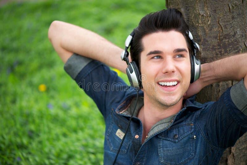 Porträt eines glücklichen Mannes, der draußen Musik hört lizenzfreie stockfotos