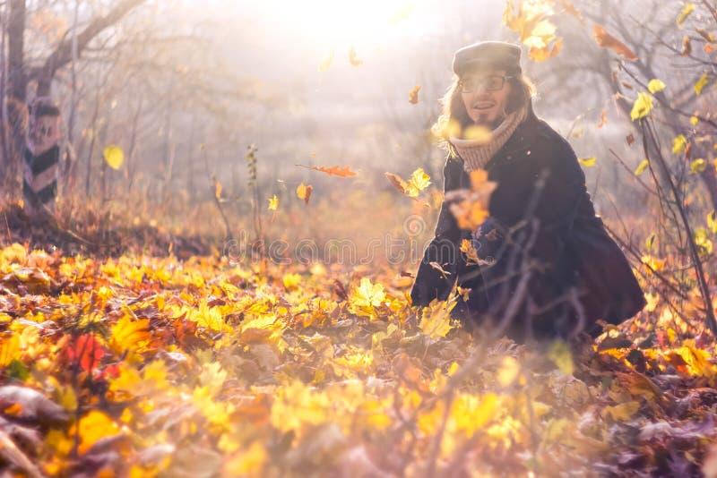 Porträt eines glücklichen Mannes, der mit Herbstlaub im Wald spielt lizenzfreie stockfotos