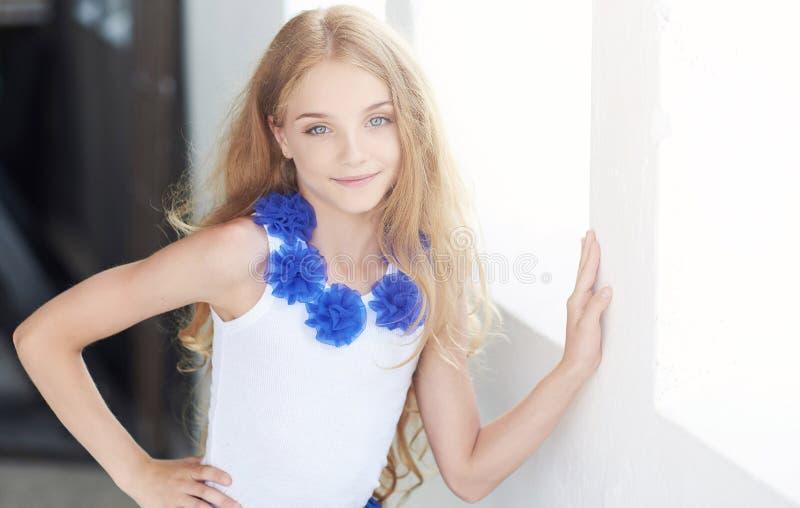 Porträt eines glücklichen Modells des kleinen Mädchens mit dem reizend Lächeln, das in einem Studio aufwirft stockfotos
