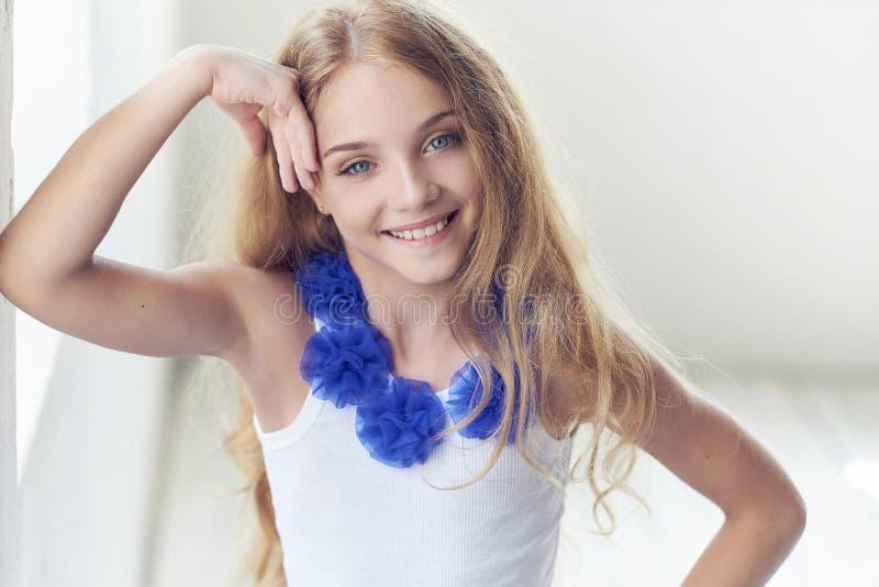 Porträt eines glücklichen Modells des kleinen Mädchens mit dem reizend Lächeln, das in einem Studio aufwirft stockfotografie