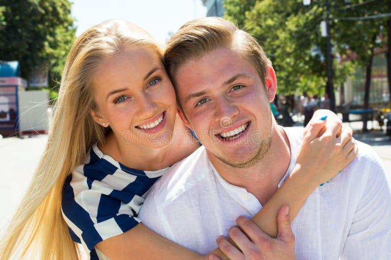 Porträt eines glücklichen Paars, das über Kamera lacht stockfotografie