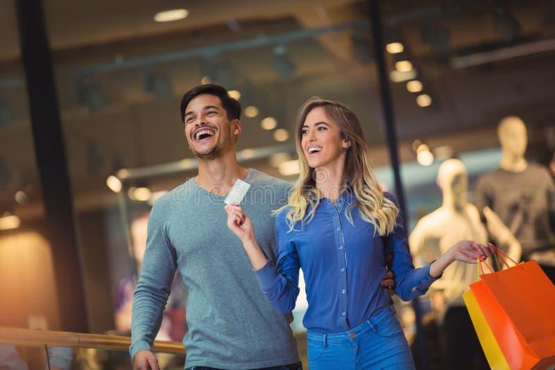 Porträt eines glücklichen Paars, das ihre neue Kreditkarte zeigt lizenzfreie stockfotografie