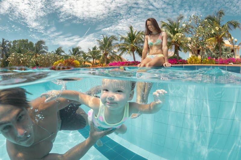 Porträt eines glücklichen Paars mit Tochter im Swimmingpool stockfotografie