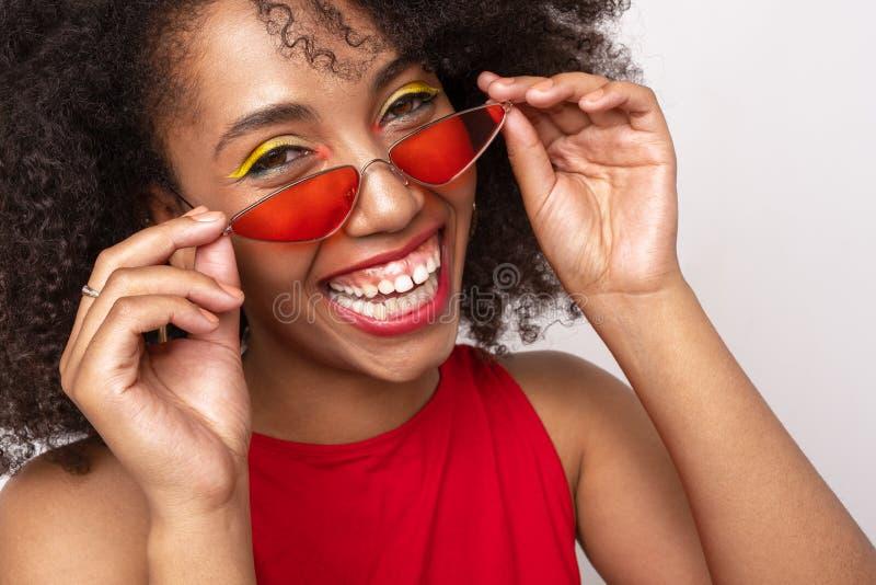 Porträt eines glücklichen schwarzen Mädchens in den roten Gläsern lizenzfreies stockfoto