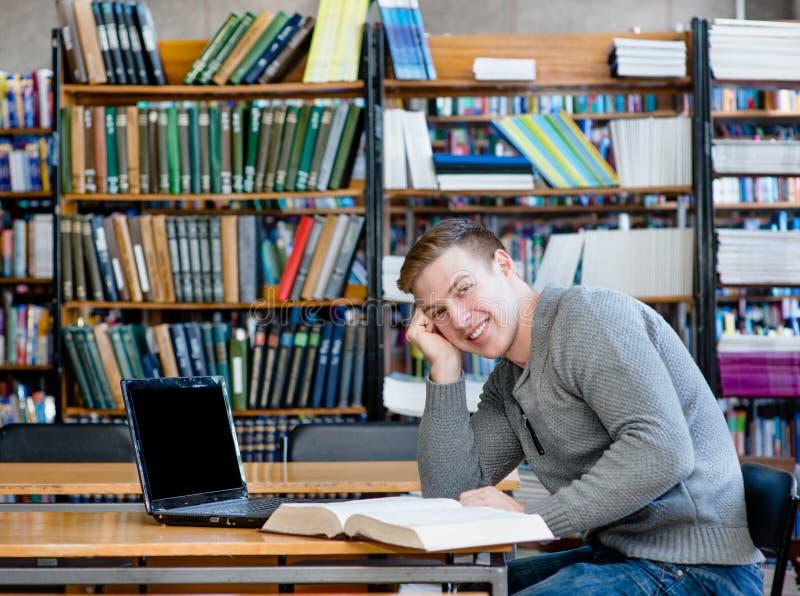 Porträt eines glücklichen Studenten mit Laptop in der Universitätsbibliothek lizenzfreie stockfotografie