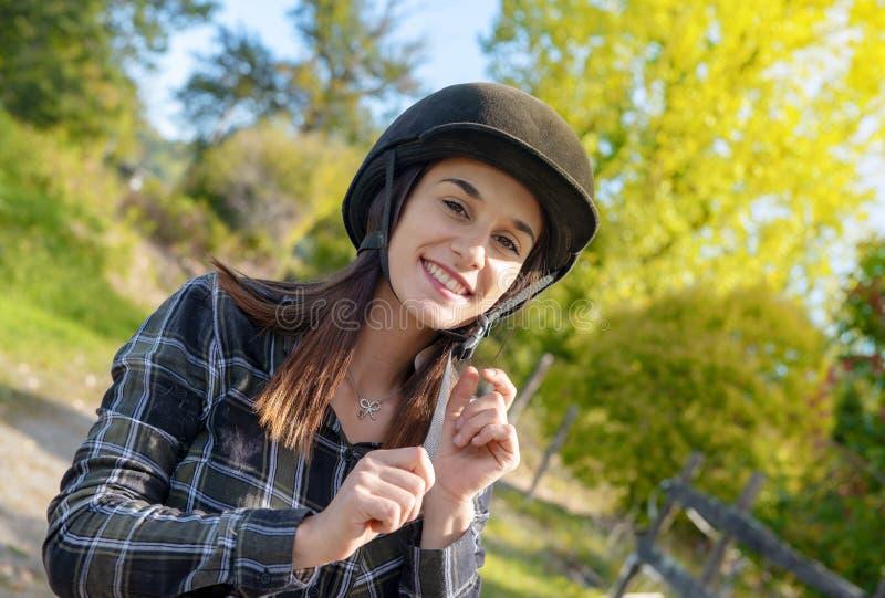 Porträt eines glücklichen weiblichen Jockeys mit Sturzhelm stockfotos