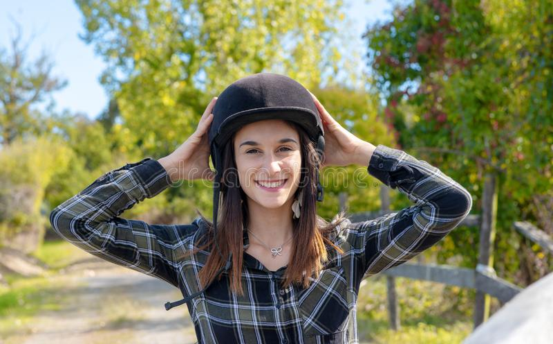 Porträt eines glücklichen weiblichen Jockeys mit Sturzhelm stockfotografie
