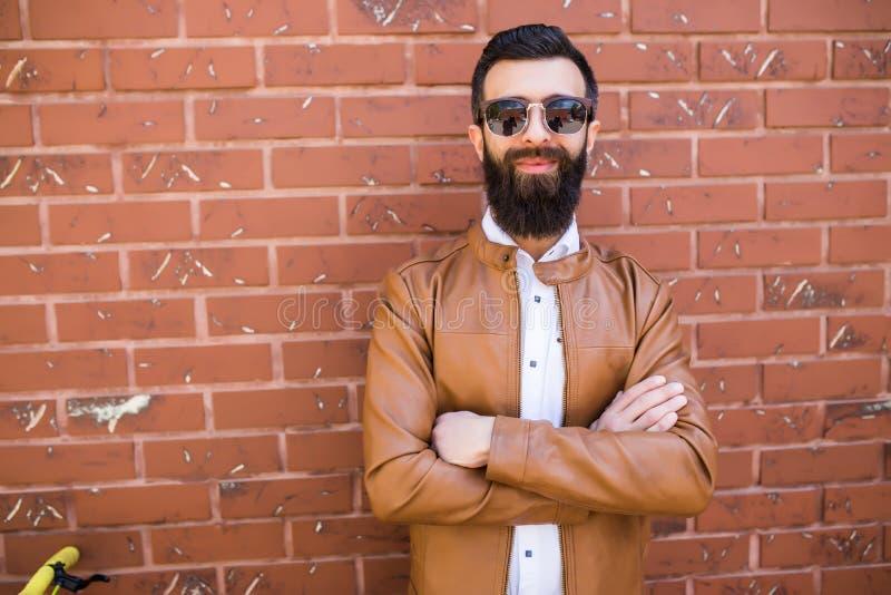 Porträt eines groben bärtigen Mannes auf Backsteinmauerhintergrund Junger stilvoller Hippie, der in der Straße aufwirft stockbilder
