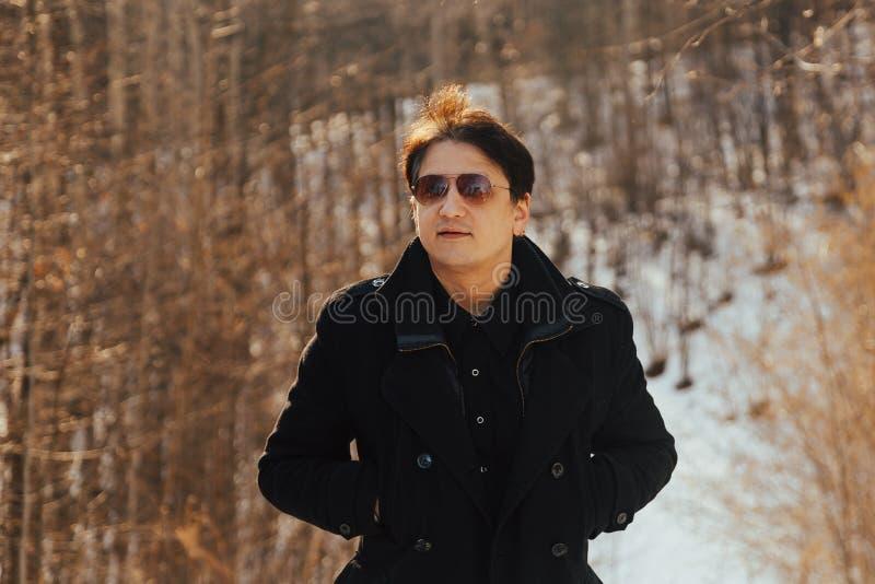 Porträt eines gut gekleidet Mannes in den Gläsern, die draußen weg schauen aufwerfen überzeugter und fokussierter Mann im Mantel lizenzfreie stockfotos