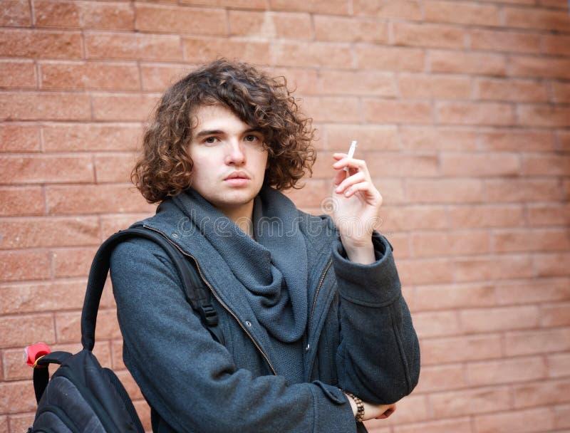 Porträt eines gutaussehenden Mannes, der gegen Backsteinmauer steht und eine Zigarette raucht stockbilder