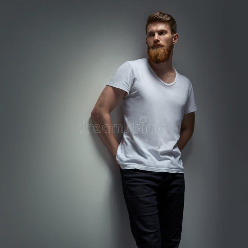 Porträt eines gutaussehenden Mannes in einem weißen T-Shirt vom Grau stockbilder