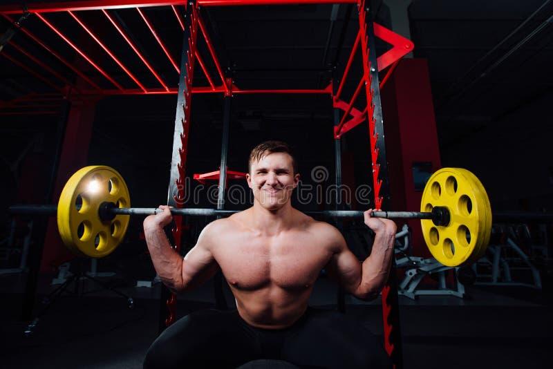 Porträt eines hübschen Athleten an der Turnhalle Mann tut die Übung mit Barbell, Stellung und dem Hocken großes überzeugtes stockfotografie