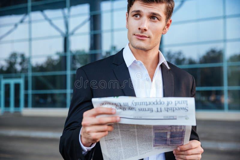 Porträt eines hübschen Geschäftsmannes, der draußen Zeitung hält stockfotos