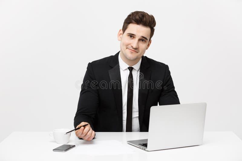 Porträt eines hübschen Geschäftsmannes, der Smartphone beim Arbeiten an einem Computer an seinem Schreibtisch hält Er ist in eine lizenzfreie stockfotografie