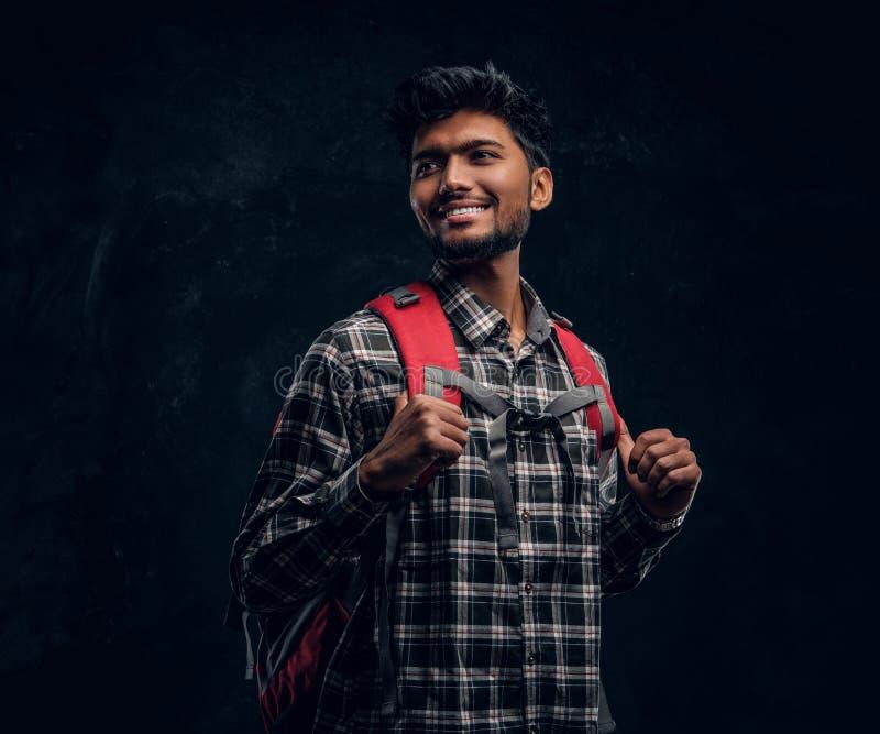 Porträt eines hübschen indischen Studenten mit einem Rucksack, der ein kariertes Hemd trägt, seitlich lächelt und schaut stockfotografie