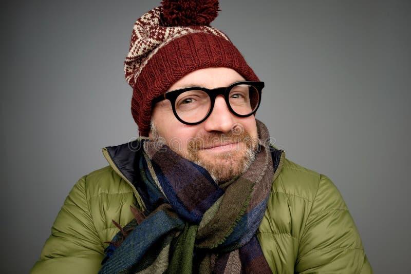 Porträt eines hübschen lächelnden tragenden warmen Wintermantels des jungen Mannes, des Schals und des lustigen Hutes stockfotografie