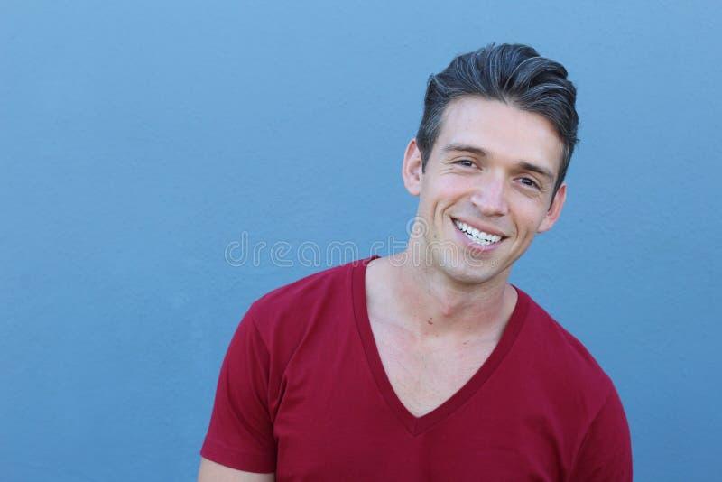Porträt eines hübschen lateinischen Mannes, der, lokalisiert über einem blauen Hintergrund lächelt stockbild