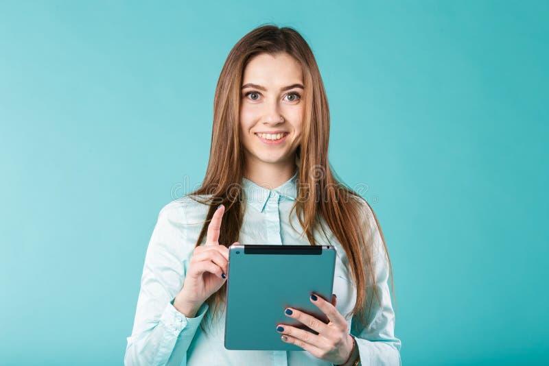 Porträt eines Haar-Bürohemdes der jungen kaukasischen Frau langen mit einer Tablette in ihren Händen, die Daumen hochhalten, sind stockfoto
