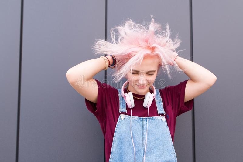 Porträt eines hellen, positiven Mädchens mit dem rosa Haar, stilvollen der Jugendkleidungs und der Kopfhörer stockfotos