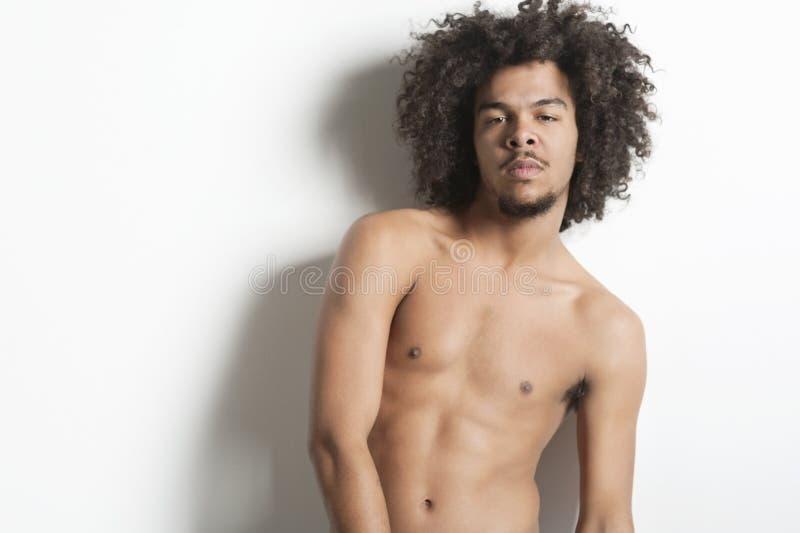 Porträt eines hemdlosen jungen Mannes über weißem Hintergrund stockbild