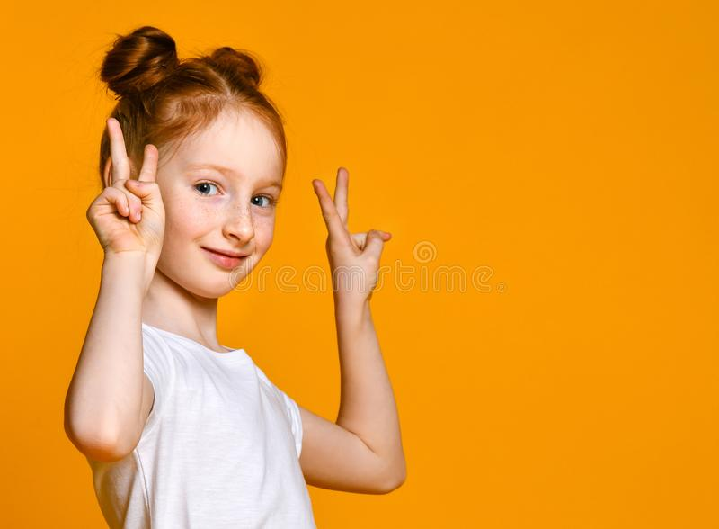 Porträt eines herrlichen rothaarigen Mädchens, das Kamera mit einem Lächeln betrachtet und Friedenszeichen mit den Fingern zeigt lizenzfreie stockbilder