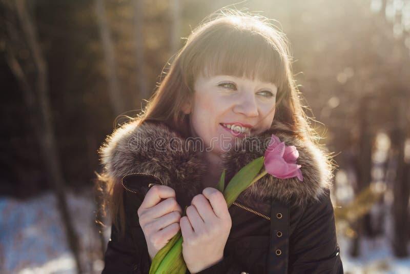 Porträt eines herrlichen schönen Mädchens in der Natur im Frühjahr mit einer Tulpe in ihren Händen stockbilder
