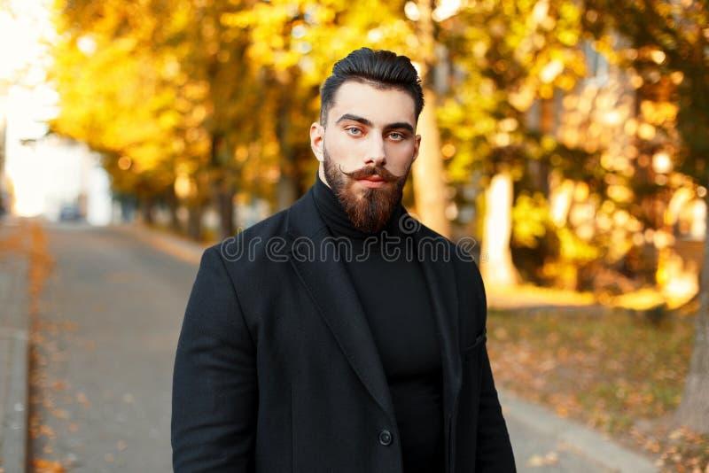 Porträt eines Hippie-Mannes mit einem Bart in einem schwarzen modischen Mantel stockfoto