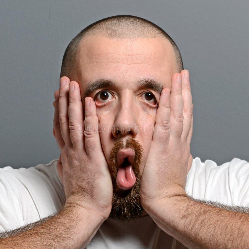 Porträt eines hoffnungslosen Mannes im Schock gegen grauen Hintergrund stockfotografie