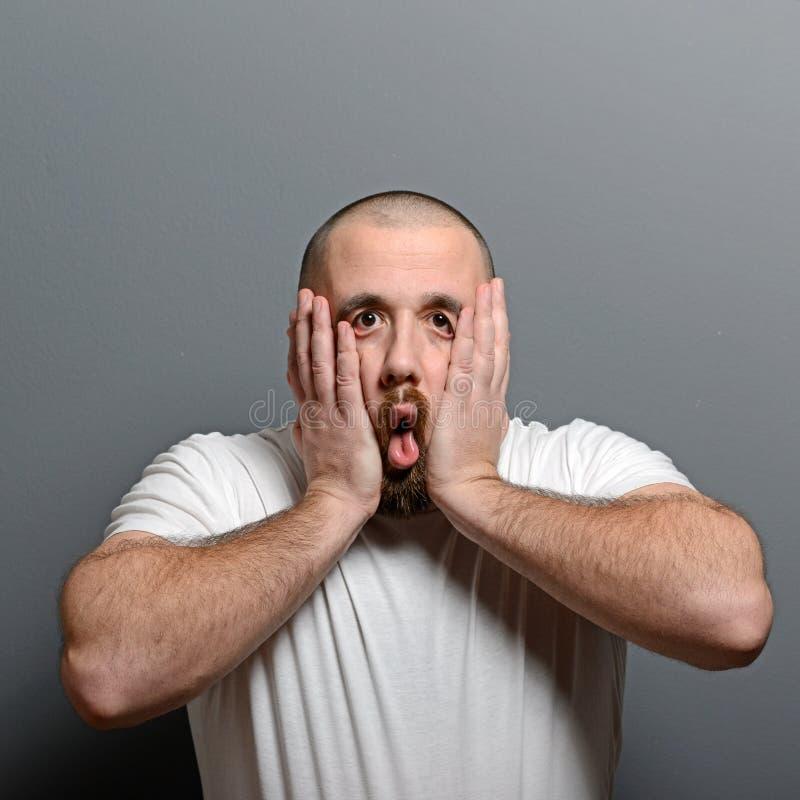 Porträt eines hoffnungslosen Mannes im Schock gegen grauen Hintergrund stockfotos