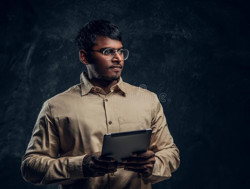 Porträt eines intelligenten indischen Mannes im Eyewear und in Hemd, die einen Tablet-Computer halten und seitlich im Studio scha stockfotografie