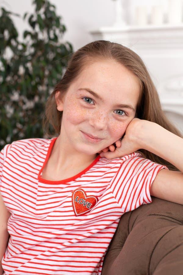Porträt eines jugendlich Mädchens der schönen Rothaarigen Nettes Mädchen, das auf dem Sofa sitzt, die Kamera lächelt und betracht stockfotografie