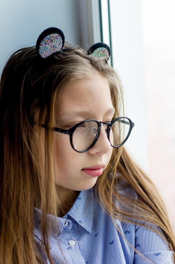 Porträt eines jugendlich Mädchens mit den Gläsern, die am Fenster sitzen lizenzfreie stockfotos