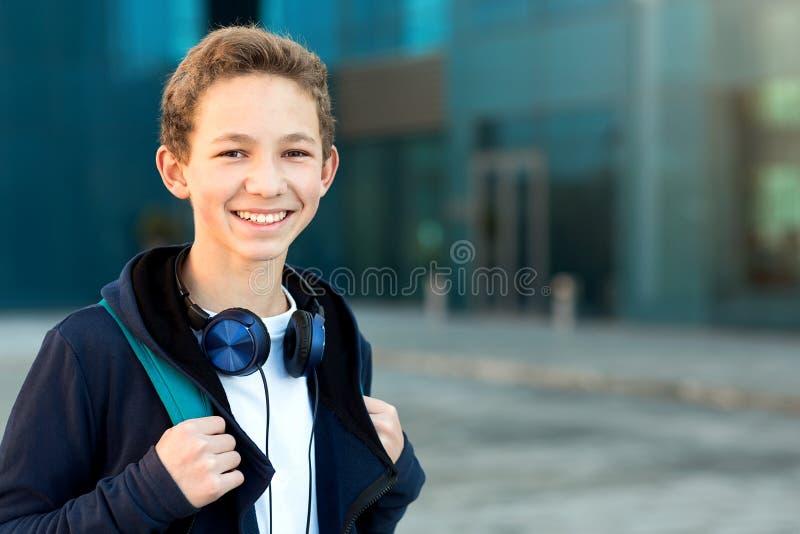 Porträt eines Jugendlichen mit Kopfhörern und Rucksack draußen Kopieren Sie Platz lizenzfreie stockbilder