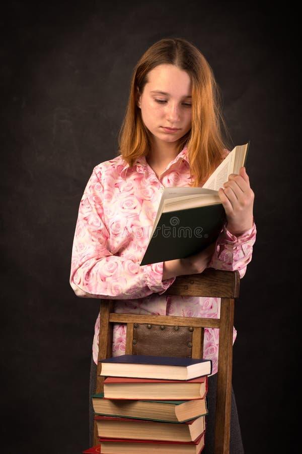Porträt eines Jugendlichmädchen-Lesebuches Stapel Bücher lizenzfreie stockfotos