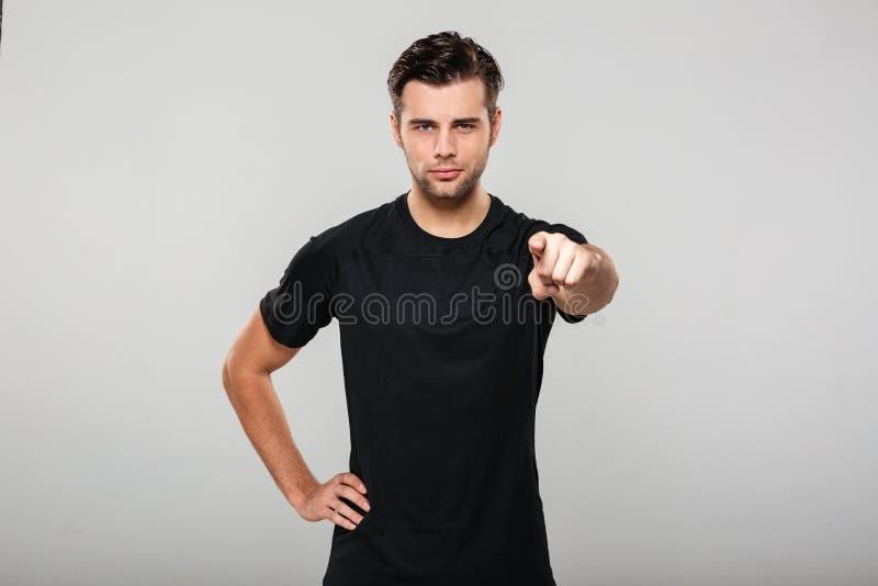 Porträt eines jungen überzeugten Sportlers, der Finger zeigt stockbilder