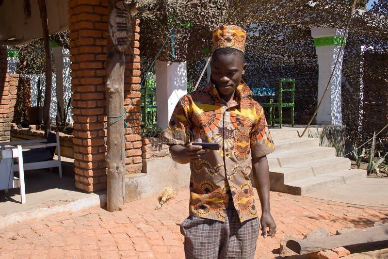 Porträt eines jungen afrikanischen Mannes, der Handy betrachtet lizenzfreies stockbild