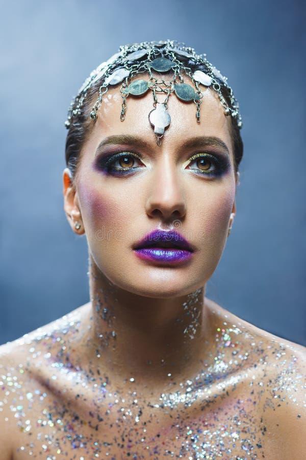 Porträt eines jungen attraktiven Mädchens mit einem kreativen Make-up und Dekorationen stockbild
