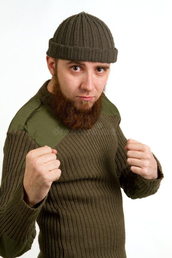 Porträt eines jungen bärtigen Kerls in einem Hut, der seine Fäuste zeigt stockfotografie