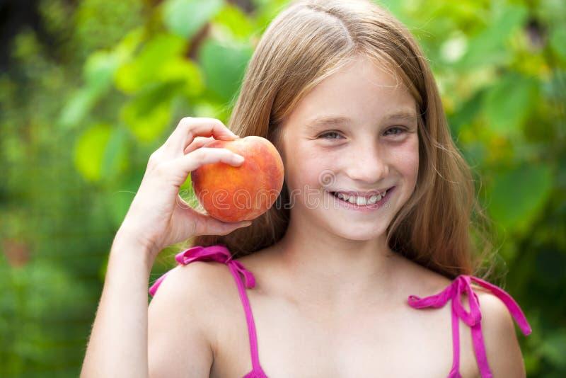 Porträt eines jungen blonden kleinen Mädchens mit Pfirsich stockbilder