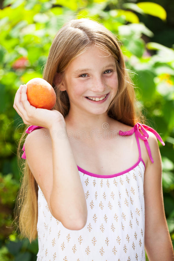 Porträt eines jungen blonden kleinen Mädchens mit Pfirsich stockfotografie