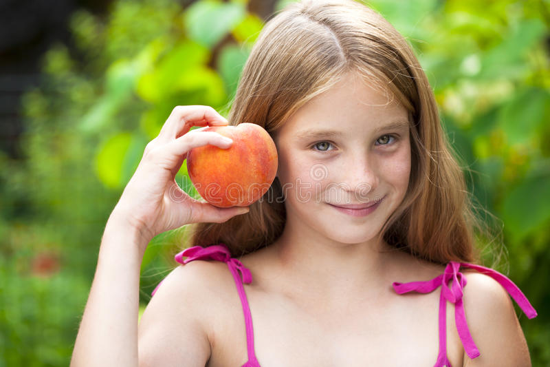 Porträt eines jungen blonden kleinen Mädchens mit Pfirsich stockfoto