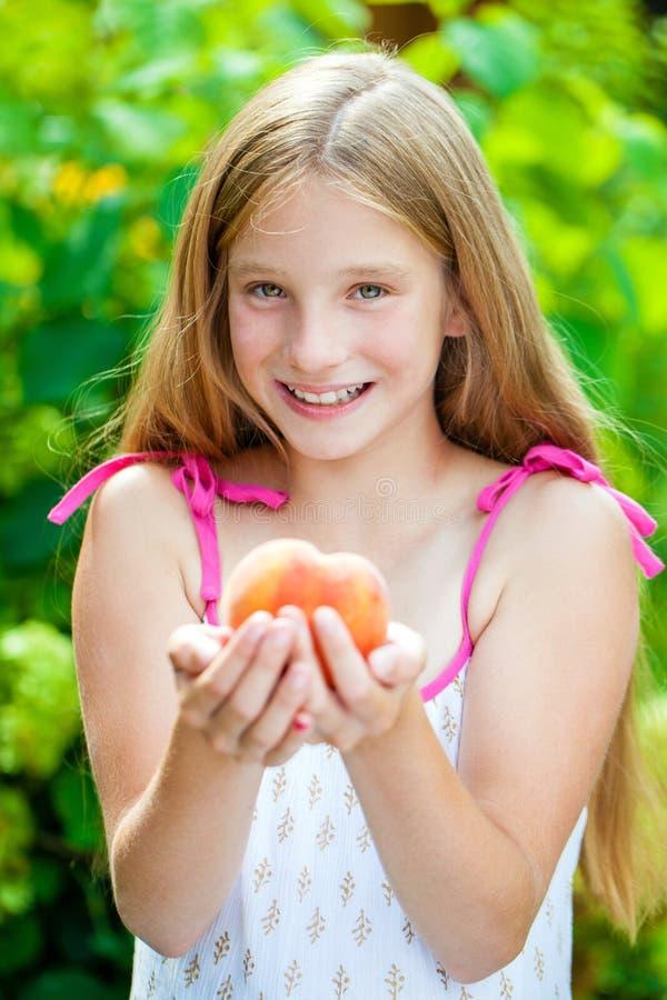 Porträt eines jungen blonden kleinen Mädchens mit Pfirsich lizenzfreies stockfoto
