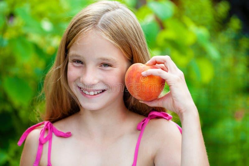 Porträt eines jungen blonden kleinen Mädchens mit Pfirsich lizenzfreie stockfotos