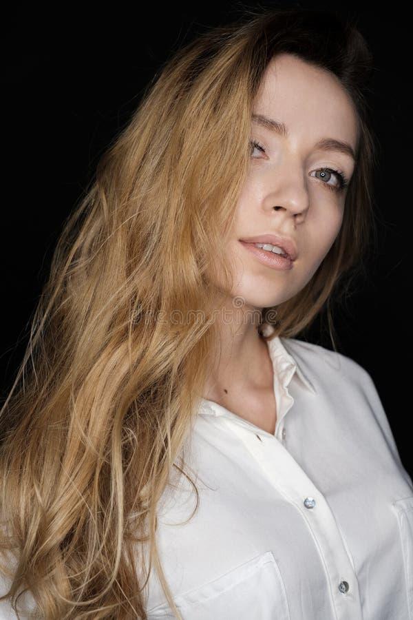 Porträt eines jungen blonden Mädchens mit dem flüssigen Haar, das die Kamera untersucht stockbilder