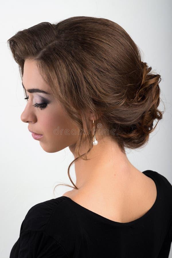 Porträt eines jungen Brunette mit dem gesammelten Glättungshaar und Make-up, Ansichtprofil stockfotografie